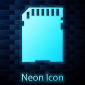 Glowing neon SD card icon isolated on brick wall background. Memory card. Adapter icon. Vector Illustration