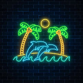 Glowing neon summer sign with palms, sun, island and jumping dolphins in ocean on dark brick wall background.