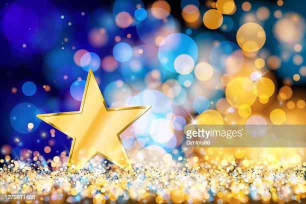 goldstar on defocused lights. blue and gold bokeh decoration - siegerehrung stock-grafiken, -clipart, -cartoons und -symbole