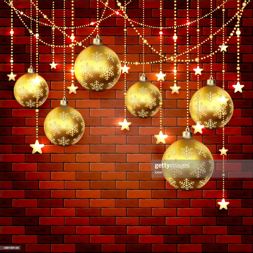Golden Christmas baubles on a brick wall