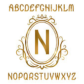 Golden letters with initial monogram in coat of arms form. Shining font and   design elements.