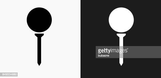 golf ball on tee icon on black and white vector backgrounds - golf ball stock illustrations