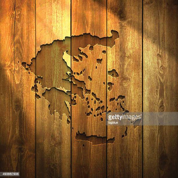greece map on lit wooden background - athens georgia stock illustrations, clip art, cartoons, & icons