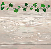 Green festive bunting with clover. Irish holiday - Happy St. Patrick's Day with garland of three-leaf. Greeting card, poster, banner. Vector on wooden background