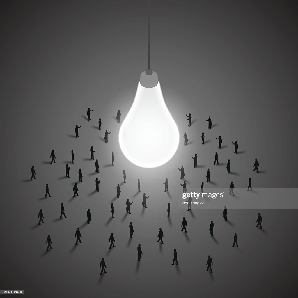 Group of people walking to a light bulb.