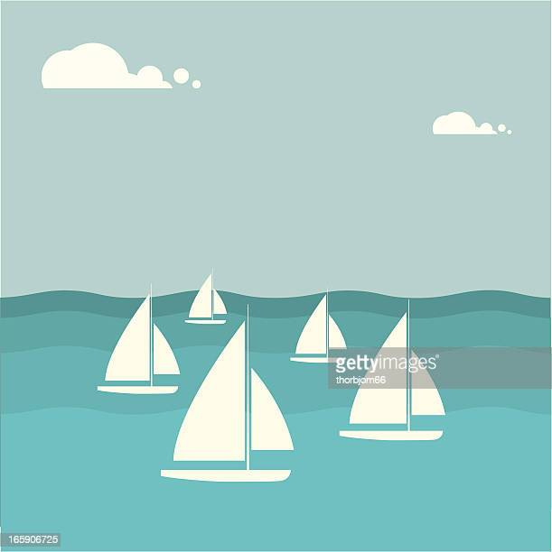 Group of sailboats on the water with clouds in background