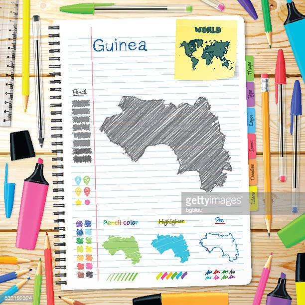 Guinea maps hand drawn on notebook. Wooden Background