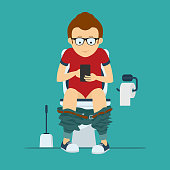 Guy hipster sits on  toilet bowl with phone in hands