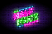 Half price, sale, premium offer neon sign on the wall.