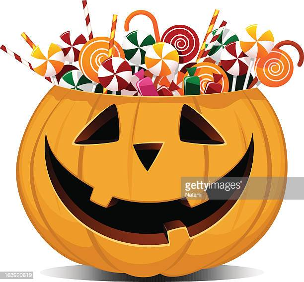 Halloween smiling pumpkin full of sweets and candies