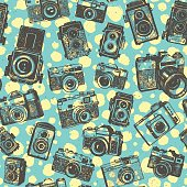 Hand drawing retro photo cameras on green font with yellow blobs of seamless pattern background