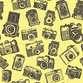 Hand drawing retro photo cameras on yellow base of seamless pattern background