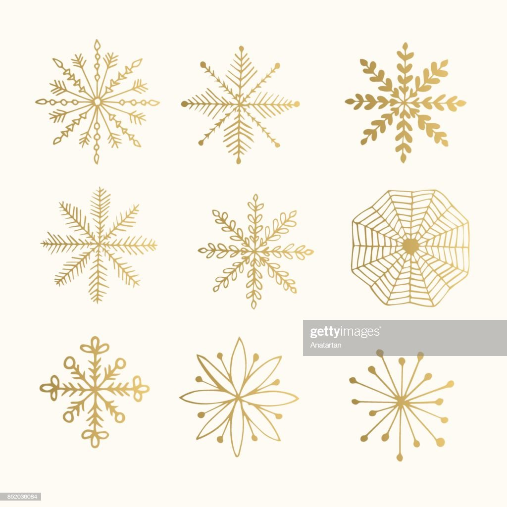 Hand drawn golden snowflakes isolated on background. Ink vector illustration.