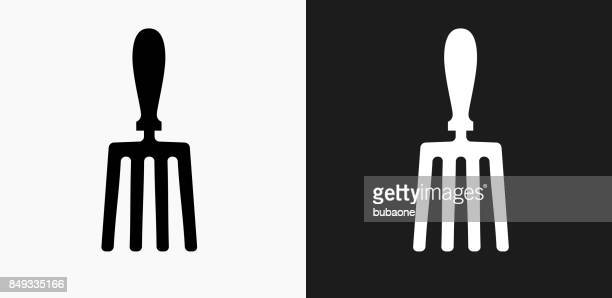 hand fork icon on black and white vector backgrounds - garden fork stock illustrations
