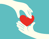 Hand giving a red heart to another hand