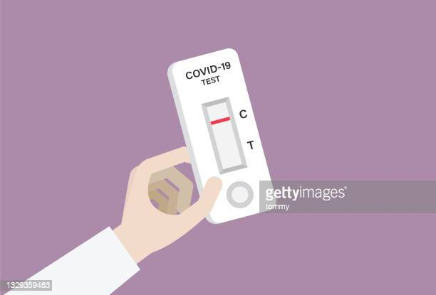 hand holding a covid-19 rapid test with a negative result - antigen stock illustrations