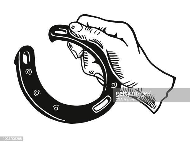 hand hält ein hufeisen - hufeisen stock-grafiken, -clipart, -cartoons und -symbole