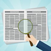 Hand holding a magnifying glass on Business news newspaper
