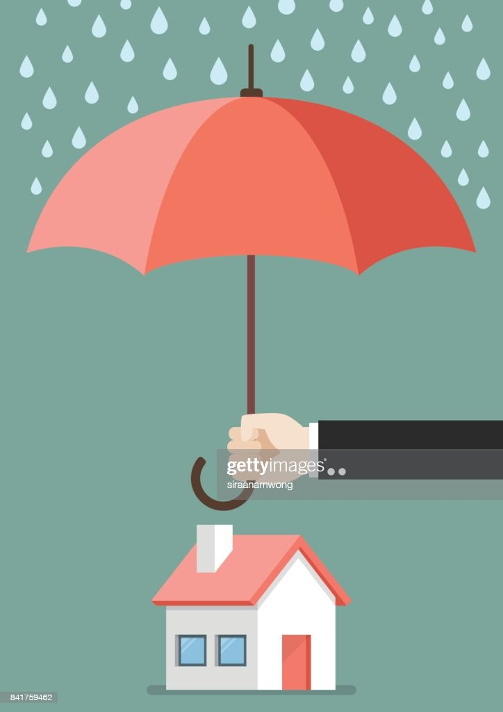 Hand holding an umbrella protecting house