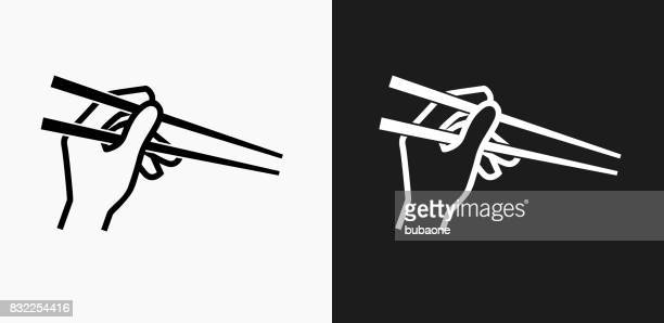 Hand Holding Chopsticks Icon on Black and White Vector Backgrounds