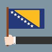 Hand holding flag Bosnia