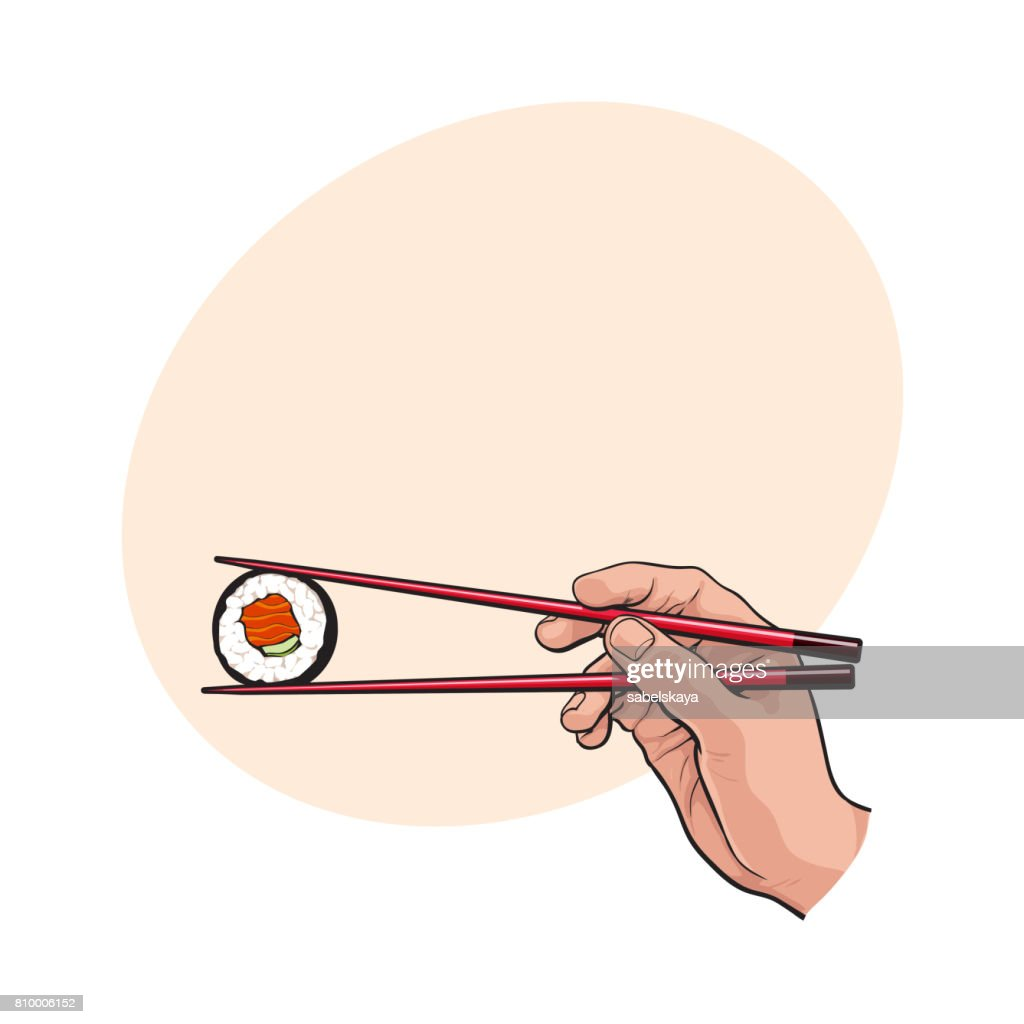 Hand holding Japanese sushi, roll with pair of wooden chopsticks