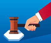 Hand holding judge's gavel