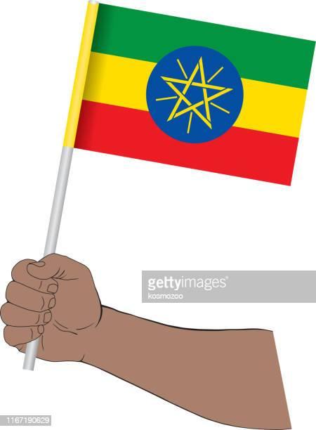 ilustrações, clipart, desenhos animados e ícones de mão que prende a bandeira nacional de etiópia - ethiopia