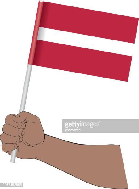 stockillustraties, clipart, cartoons en iconen met hand houden nationale vlag van letland - letland