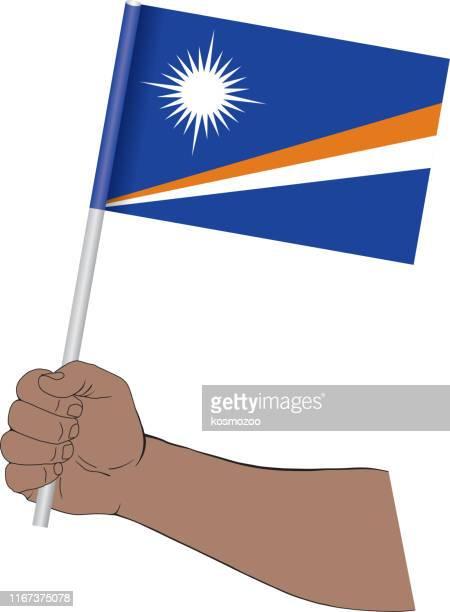 hand holding national flag of marshall islands - marshall islands stock illustrations, clip art, cartoons, & icons
