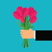 Hand holding pink tulip flowers bouquet