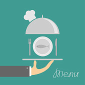 Hand holding silver platter cloche with chefs hat and plate fish, fork, knife. Menu card. Green background. Flat design.