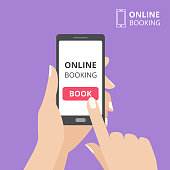 Hand holding smartphone with book button on screen. Concept of online booking mobile application.