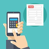 Hand holding smartphone with calculator on screen and tax form
