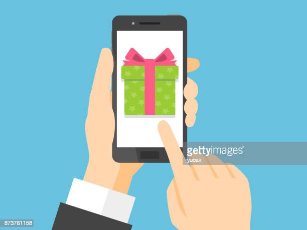 hand holding smartphone with gift box on the screen - holding stock illustrations, clip art, cartoons, & icons