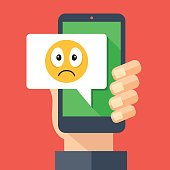 Hand holding smartphone with sad emoji message on screen. Sad emoticon icon. Social networking, IM, SMS, instant messaging on mobile device, online chat concepts. Modern flat design vector illustration