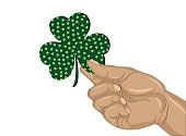 Hand holds ornate clover tree-leaf. Celebration concept St. Patrick's Day. Greeting card. Vector illustration on a white background. Free space for your text and labels