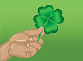 Hand holds ornate clover tree-leaf. Celebration concept St. Patrick's Day. Greeting card. Vector illustration on a green background. Free space for your text and labels