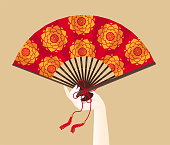 A hand of geisha holding a red fan