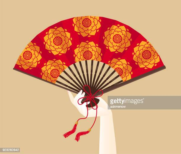 a hand of geisha holding a red fan - japanese culture stock illustrations