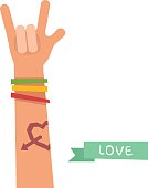 Hand with Love tattoo and colorful friendship bracelets