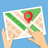 Hands holding city map with map marker flat illustration