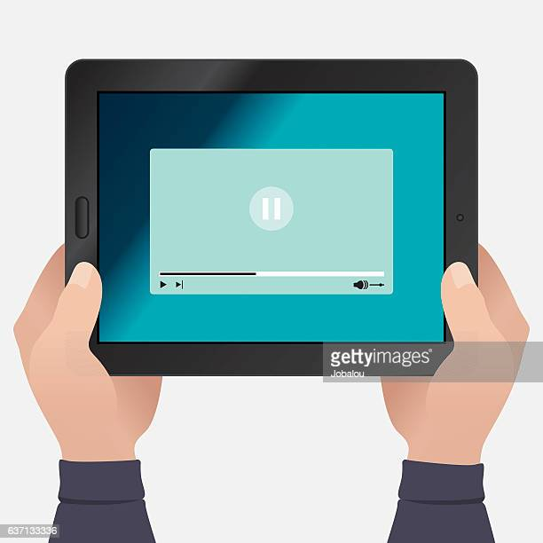 Hands Holding Tablet With Paused Video