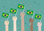 Hands Holding Up Brazil Flags