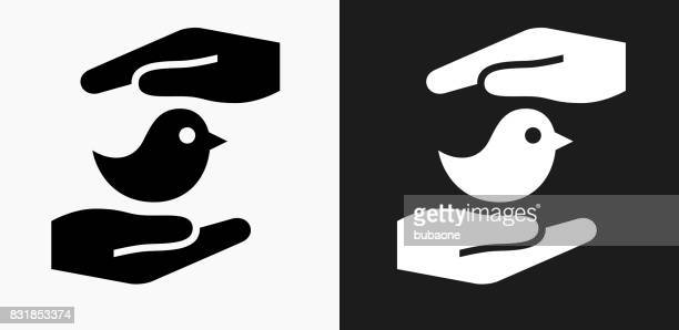 Hands Saving Bird Icon on Black and White Vector Backgrounds