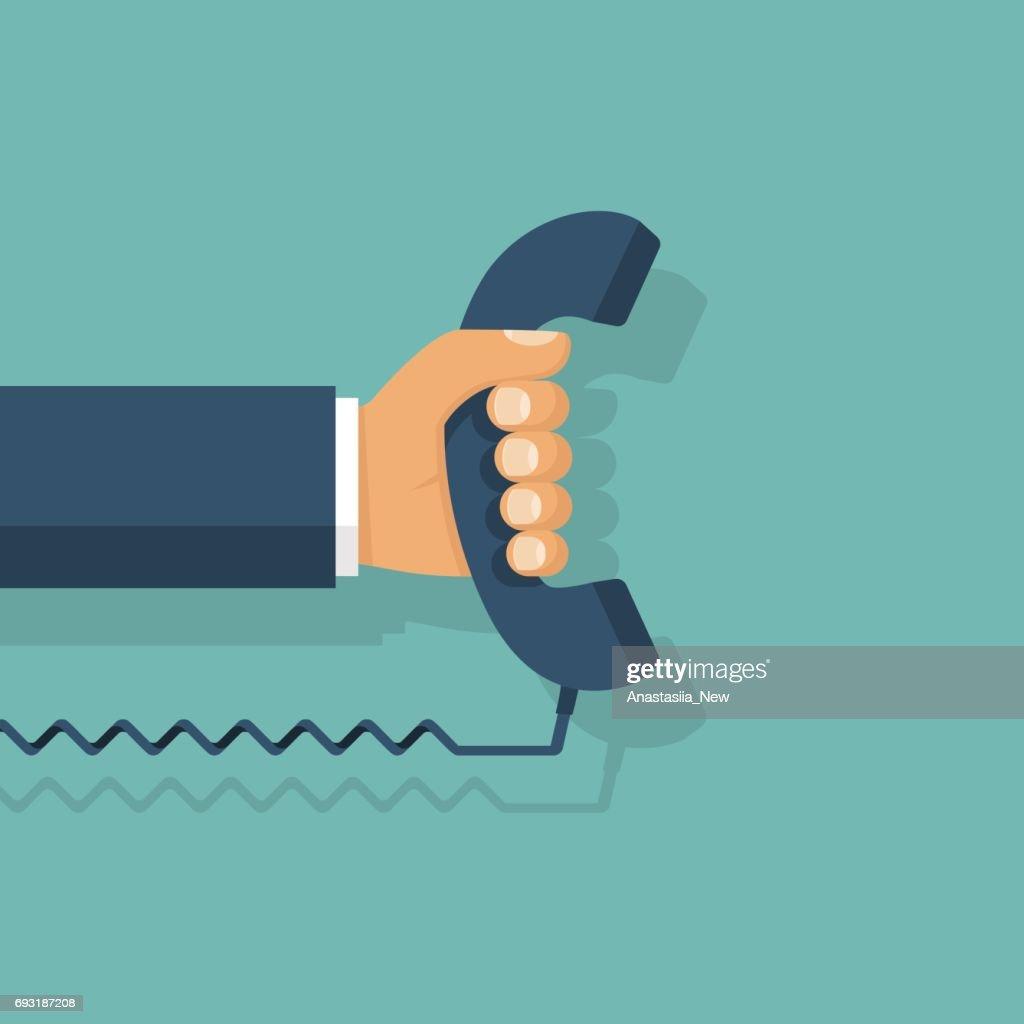 Handset in hand. Holding telephone
