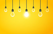 Hanging light bulbs with glowing one on a yellow background