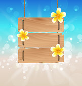Hanging wooden signboard with tropical flowers frangipani