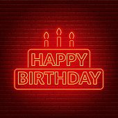 Happy birthday neon sign. Birthday card in the shape of a cake with candles on a dark background.