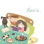 Happy couple in bed with cats and dog